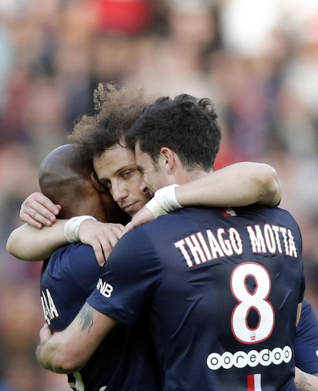David Luiz é abraçado pelos companheiros ao marcar o primeiro gol no jogo contra o Lens neste sábado, 7 de março de 2015.