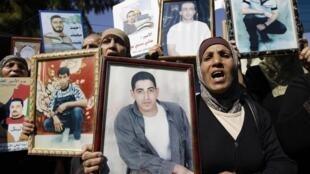 Manifestantes exibem fotos de prisioneiros palestinos em Israel.
