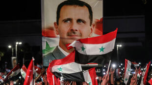 Syrians wave national flags and carry a large portrait of their president as they celebrate in the streets of the capital Damascus, a day after Bashar al-Assad wa selected to a fourth term with an overwhelming majority, according to official results