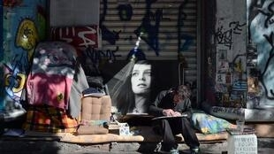 A homeless man draws a picture next to his belongings in central Athens
