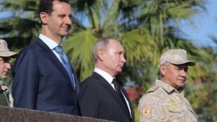 O Presidente Vladimir Putin rodeado pelo Ministro  da Defesa russo Sergeï Choïgu e pelo seu  homólogo  sírio Bashar al-Assad durante a visita  a  base aérea  de Hmeimim na Província de Latakia, na Síria.11 de Dezembro de 2017
