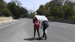 Des Indiens marchent dans une rue déserte de New Delhi dont l'air n'a jamais été aussi pur depuis le début des mesures de confinement imposées par le gouvernement.
