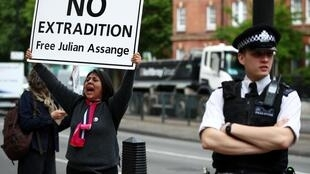 A demonstrator protests as a police officer stands guard outside of Westminster Magistrates Court, where a case hearing for US extradition of  Julian Assange is held