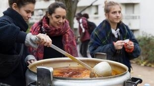 Volunteers with the Midi du MIE serve up lunch to unaccompanied minor migrants in Paris