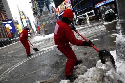 Garis removem a neve nas ruas desertas de Times Square, neste sábado, 9 de fevereiro.