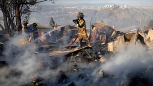 Les pompiers travaillent pour éteindre l'incendie qui s'est déclaré à Valparaiso, dans le centre du Chili, le 24 décembre 2019.