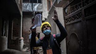 Un membre de l'équipe d'évalution du séisme affecté aux bâtiments vérifie un immeuble endommagé à Katmandu, le 2 mai.