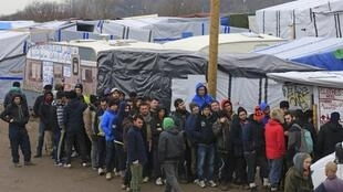 """Migrantes fazem fila para receber roupas no campo de refugiados de Calais conhecido como a """"selva""""."""
