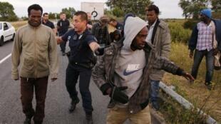 Polícia francesa intercepta migrantes clandestinos perto do acesso ao Eurotúnel, em Calais, na França, neste 3 de agosto de 2015.