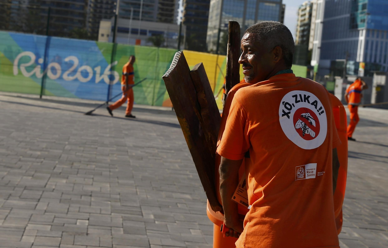 Des travailleurs portent des combinaisons  avec une inscription sur le dos  «Chasse à  Zika» dans le village olympique, le 30 juillet 2016.