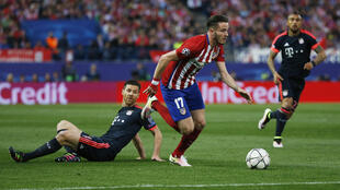 Saul Niguez goes past Bayern Munich's Xabi Alonso before scoring the first goal for Atletico Madrid.
