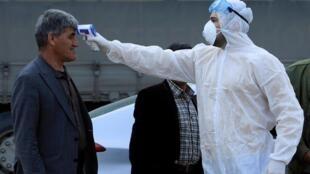 Un personnel médical contrôle la température des personnes à un point de passage de la périphérie de Duhok, en Irak, le 2 mars 2020.