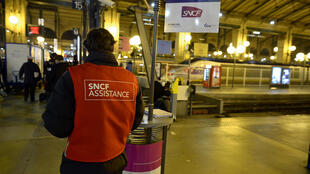 An employee in charge of commuters information stands at the Gare du Nord train station in Paris, 11 December, 2013