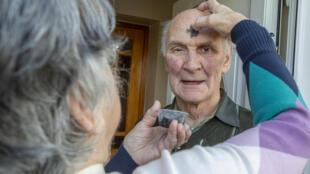 Sally McDonald, residente de Clonmany, en el condado irlandés de Donegal, bendice a su esposo Mac con cenizas distribuidas a principios de la Cuaresma, el 17 de febrero de 2021