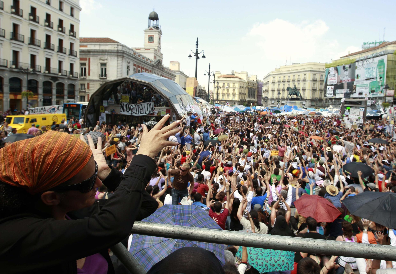 Miles de manifestante oyen el discurso de un miembro del movimiento de los 'indignados' españoles, en la  Puerta del Sol de Madrid, el 29 de mayo de 2011.