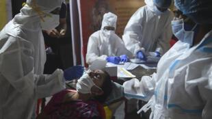 Personal sanitario toma una muestra de mucosa nasal a una mujer para realizar una prueba de detección del coronavirus, el 16 de septiembre de 2020 en la ciudad india de Bombay