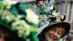 Женщина с лепреконом на шляпе во время парада в День св. Патрика в Дублине. 17 марта 2018 г.