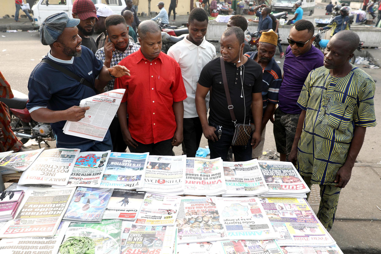 Watu wakikusanyika mbele ya duka la kuuza magazeti baada ya uchaguzi wa urais kuahirishwa Nigeria, Februari 16 Lagos.