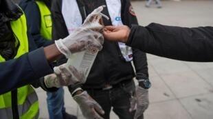 Un jeune volontaire portant des gants de protection offre un désinfectant pour les mains lors d'une campagne d'information sur la maladie à coronavirus, dans la banlieue de Tensta à Stockholm, Suède le 12 avril 2020.
