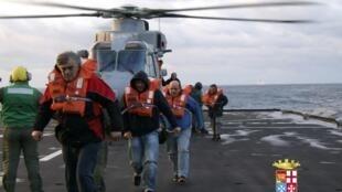 Des passagers arrivent sur le navire de la marine italienne «San Giorgio» après avoir été secourus du «Norman Atlantic» en feu.