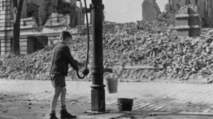 Un garçonnet allemand allant chercher de l'eau au puits, dans la ville de Magdebourg, ayant subit des bombardement pendant la Seconde Guerre mondiale.