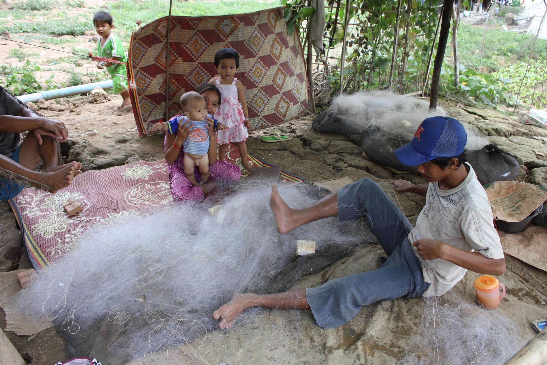 Một ngư dân người Việt ở Xóm Mới, ngoại ô Phnom Penh, đang ngồi vá lưới