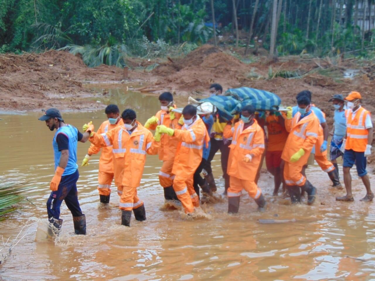 Rescue officials of the National Disaster Relief Force carry a body that was submerged in floods in Kerala.