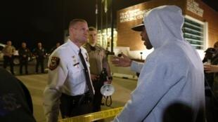 Morador de Ferguson e policiais discutem em frente à delegacia de polícia da cidade nesta quinta-feira (12).