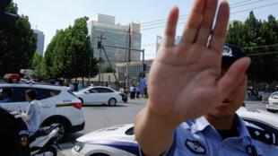 Un officier de police chinois tente d'empêcher une prise de vue devant l'ambassade américaine à Pékin, après l'explosion, jeudi 26 juillet 2018.