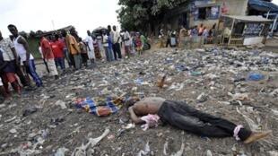 Corps gisant au sol les mains et les pieds liés, à Abobo le 8 février 2011.