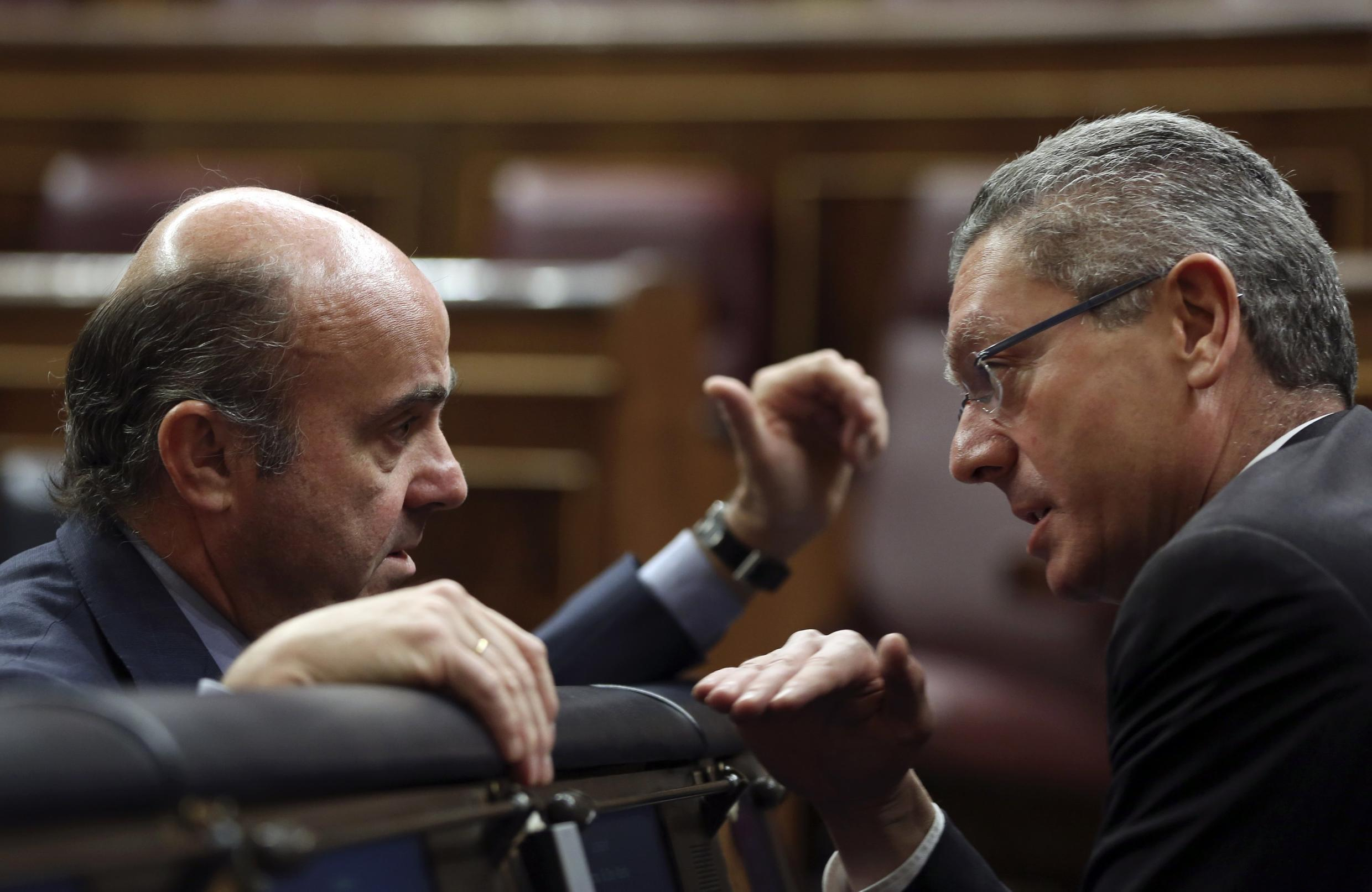 Spain's Economy Minister Luis de Guindos talks to Justice Minister Alberto Ruiz-Gallardon before the start of the 2014 budget debate at Parliament in Madrid