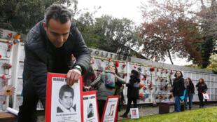 Un homme avec le portrait d'une personne disparue durant le régime autoritaire du général Pinochet. Le 11 septembre 2017.
