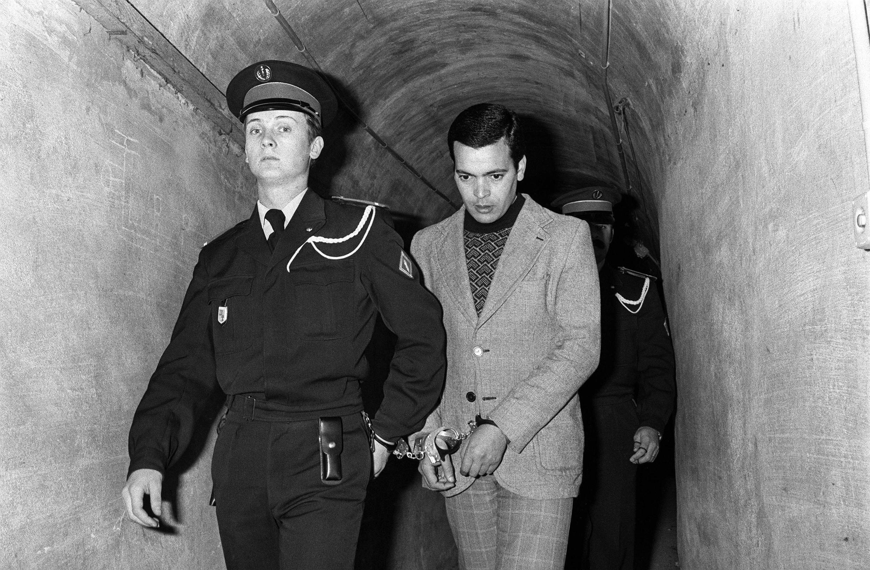 Полицейские ведут Хамида Джандуби по коридору тюрьмы в суд в городе Экс-ан-Прованс, Франция, 24 февраля 1977 г.