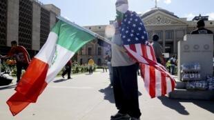 Un manifestant proteste devant le Capitole, à Phoenix, tenant à la main les drapeaux américain et mexicain ce jeudi 23 avril 2010.