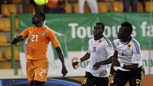Emmanuel Eboue (L) of Côte d'Ivoire heads the ball while Miguel Geraldo Quiami (C) and Dani Massunguna of Angola look on