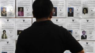 Dans un bureau de vote de Bangkok un électeur consulte les profils des candidats, dimanche 30 mars 2014.