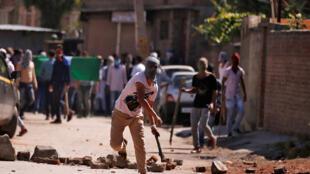 Un manifestant jette une pierre contre la police indienne, en marge d'un rassemblement le 28 juillet 2016 à Srinagar, après les violences meurtrières survenues au Cachemire.