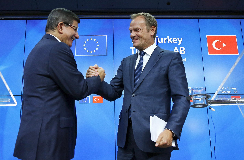 O primeiro-ministro turco, Ahmet Davutoglu, e o presidente do Conselho Europeu, Donald Tusk, anunciam o acordo em Bruxelas.