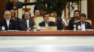 Iranian President Mahmoud Ahmadinejad (C) sits next to his delegation during the closing session of the Shanghai Cooperation Org