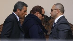 Italian Prime Minister Silvio Berlusconi (C), flanked by his bodyguards, arrives at Grazioli palace in downtown Rome 12 July 2011.
