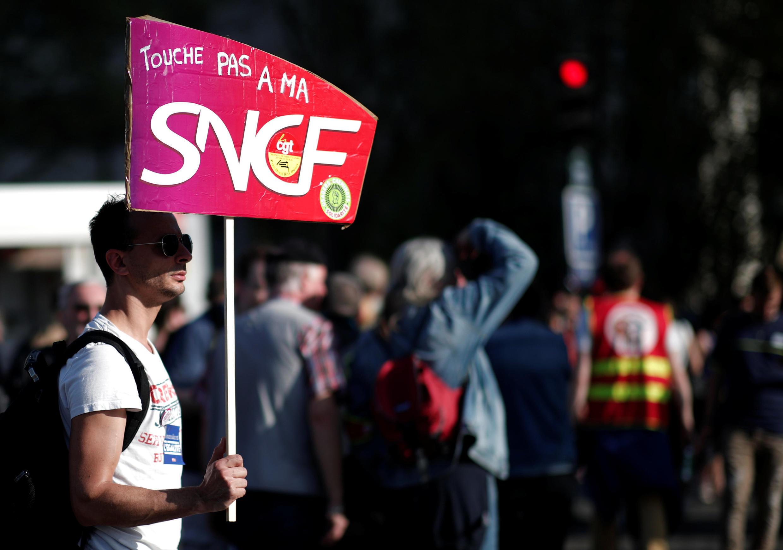 Un manifestant brandit une pancarte en soutien à la SNCF pendant un rassemblement contre la réforme du gouvernement à Paris, le 19 avril 2018.