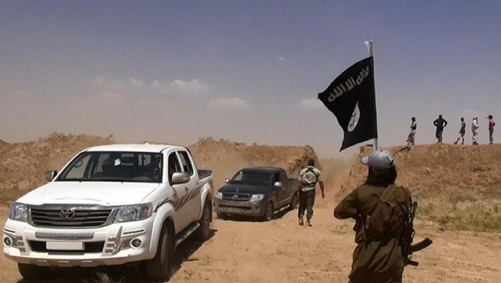 Mpiganaji wa Dola la Kiislam akishikilia bendera nyeusi ya Islamic State, karibu na mpaka wa Iraq na Syria.