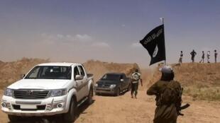 Mpiganaji wa kundi la Islamic State akishikilia bendera nyeusi ya Islamic State, karibu na mpaka wa Iraq na Syria.