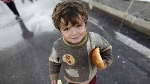 A Syrian refugee boy holds bread at the Boynuyogun refugee camp on the Turkish-Syrian border in Hatay province