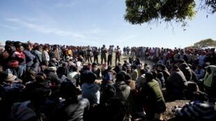 Après avoir fui les troubles en Libye, des travailleurs bangladais immigrés attendent de récupérer leur passeport dans un camp de réfugiés à Ras Jdir, à la frontière entre la Libye et la Tunisie, le 6 mars 2011.