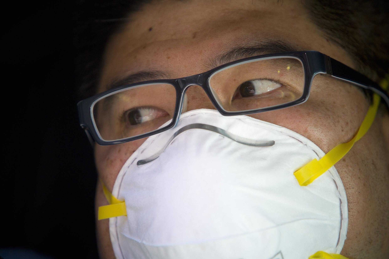 Contre l'épidémie de grippe qui frappe l'Etat de New York, un homme porte un masque chirurgical, à Chinatown, New York, le 10 janvier 2013.