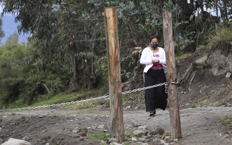 Une indigène passe devant une chaîne qui interdit le trafic de véhicules et de personnes à Cotacachi, en Équateur, dimanche 21 juin 2020. Des blocus ont été établis pour empêcher la propagation du virus dans certaines villes (image d'illustration).