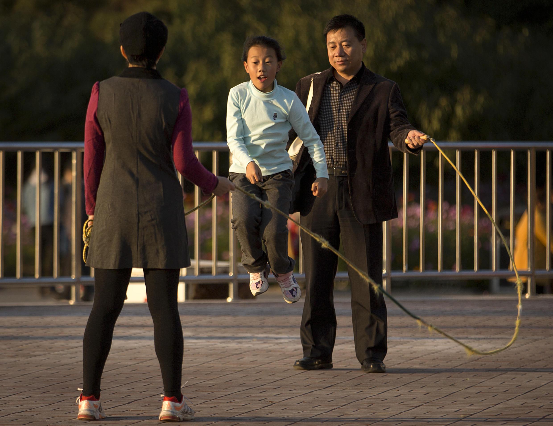Archivo. Un hombre y una mujer hacen girar una cuerda para saltar a una niña en un parque de Beijing, el 31 de octubre de 2015.