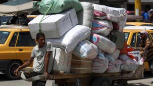 Un trabajador transporta mercadería en bolsas apiladas en un carrito frente al mercado de Shorja en la capital iraquí, Bagdad, el 4 de mayo de 2020, durante la nueva crisis pandémica de coronavirus.