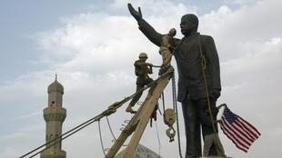 US Marines chain the head of a statue of Saddam Hussein before pulling it down in Baghdad's al-Fardous square, 9 April 2003